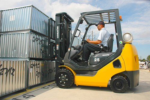 Man Operating Forklift to Lift Containers